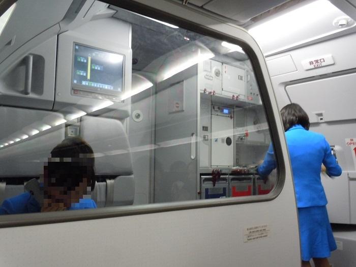 機内最前列にて出発前の最終チェックを行うバニラエアのCAさん