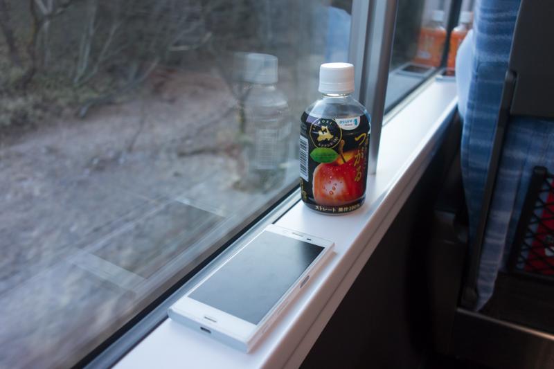 E353系の窓側面のちょっとしたスペースに置かれたスマホとペットボトル