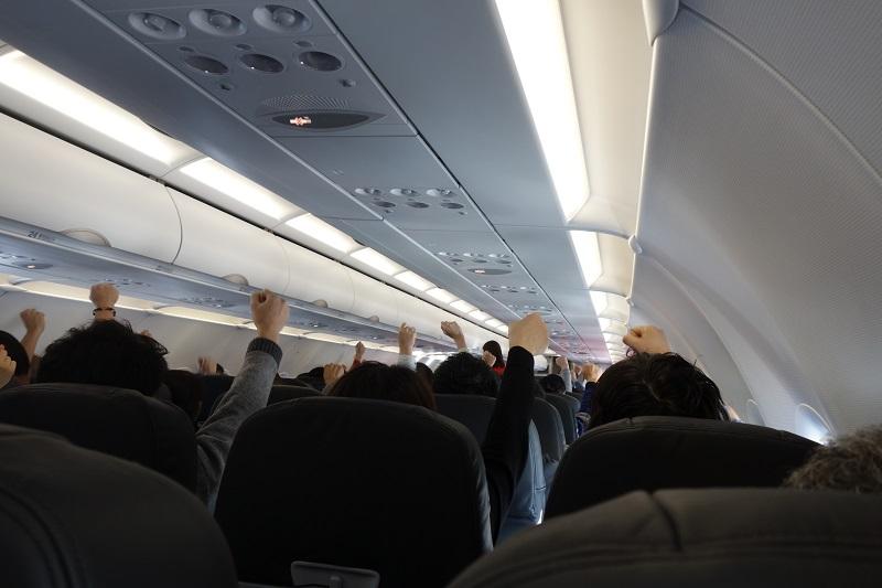 機内でのじゃんけん大会にて手を上げる乗客の様子