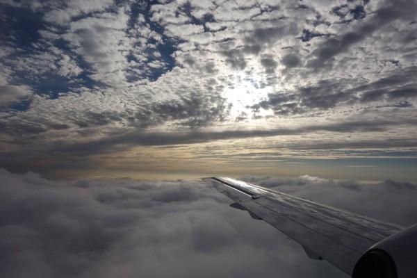 雲と雲の間を飛行する搭乗機