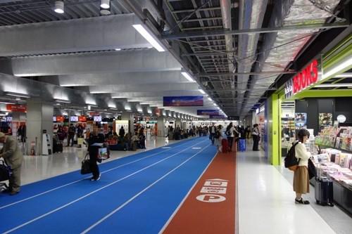 まるで陸上競技場のような床の雰囲気の成田空港第3ターミナル内の様子