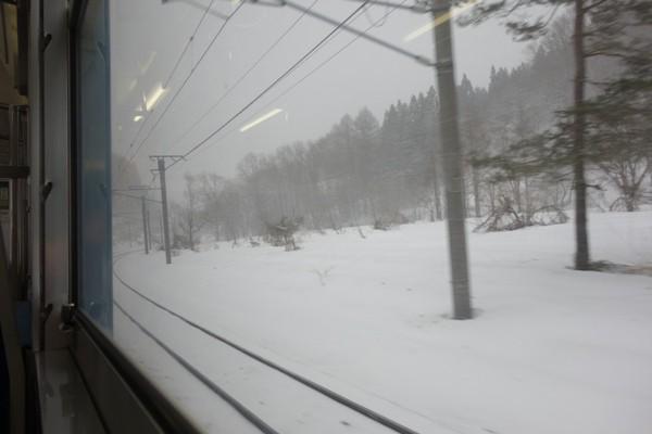 雪の中を爆走する115系の車内からの景色