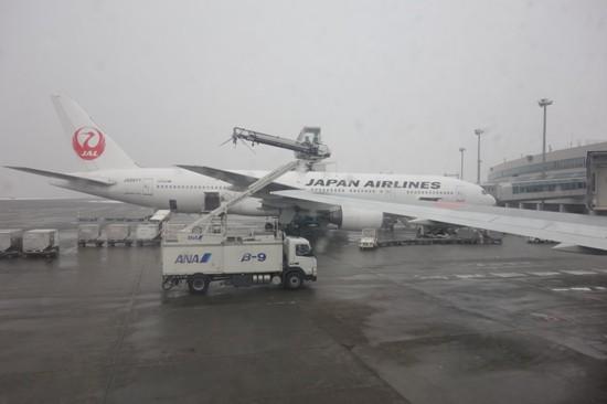 真冬の新千歳空港にてデアイシングを行う作業車。