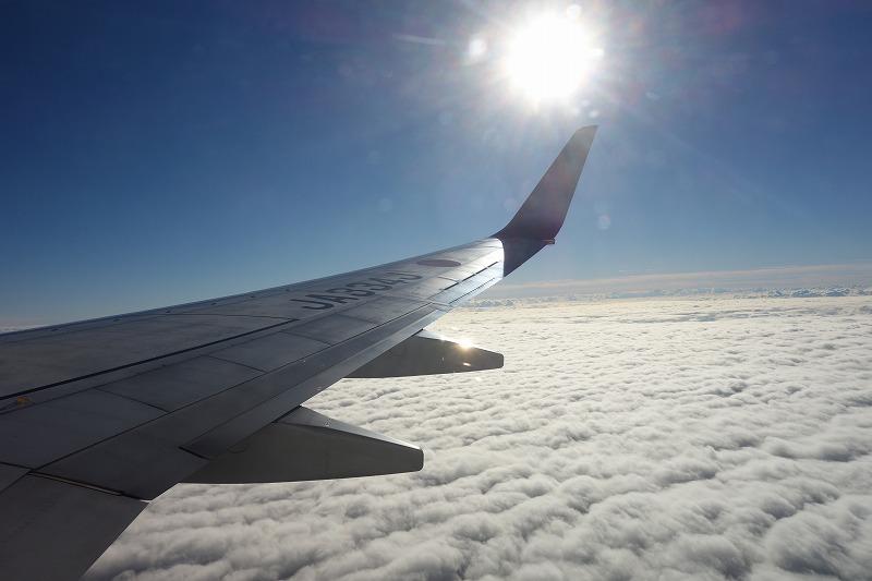 雲の絨毯の上を飛行する搭乗機から撮影した景色