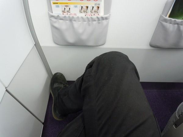 最前列の座席で足を組んだ様子