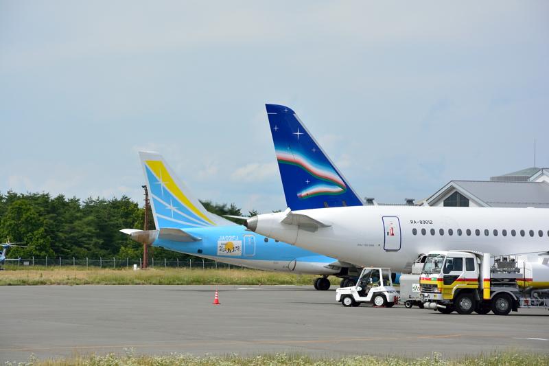 松本空港に飛来したヤクーツク航空のSSJ-100型機とFDAのE170型機の尾翼